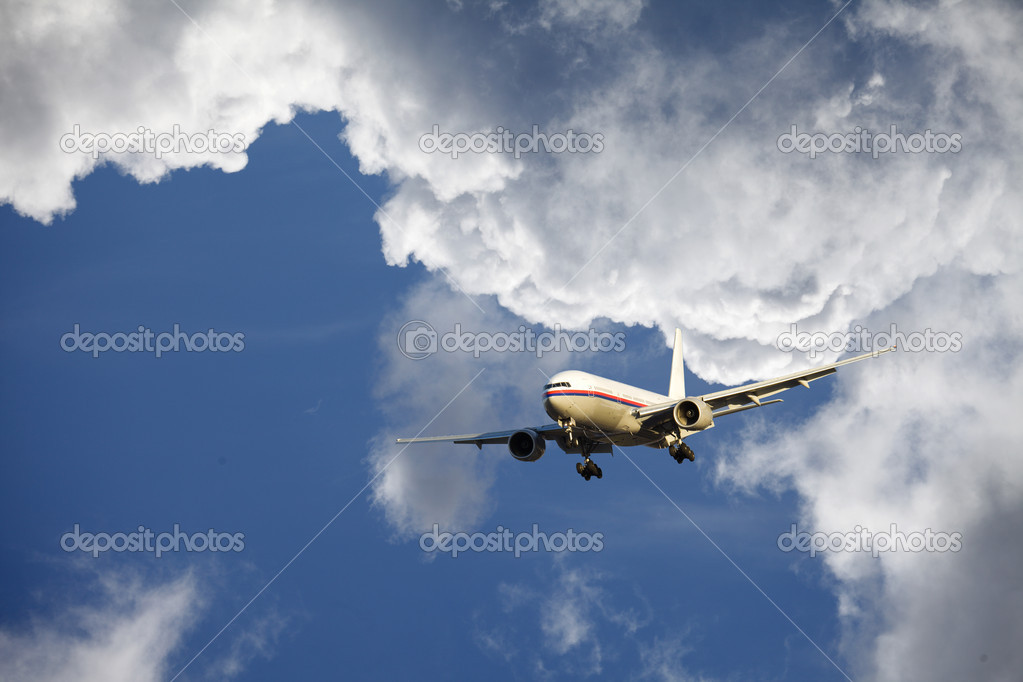 Airplane flying through a dramatic cloudscape, sunset — Stock Photo #12579486