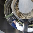 Airline pilot checking jet engine - Stock Photo