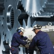 Steel engineers working a gears machinery — Stock Photo