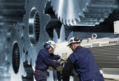 Steel engineers working a gears machinery — Stock Photo