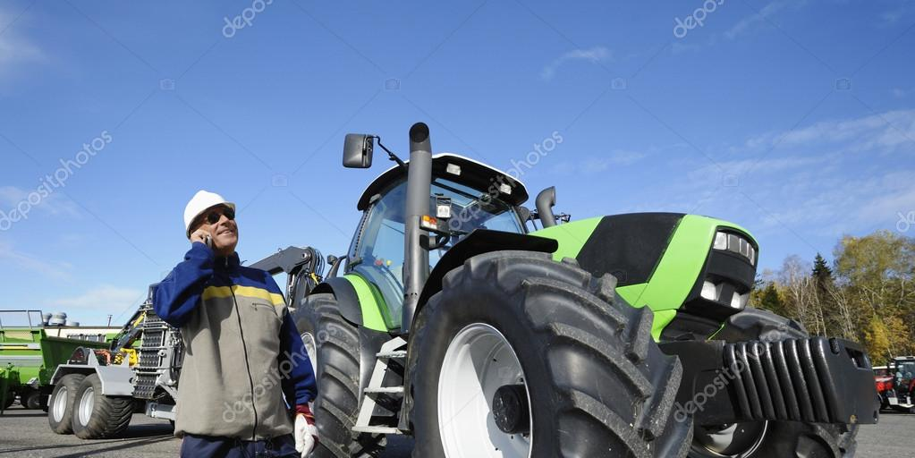 Modern farmer talking in phone, large tractor and plough in the background — Stock Photo #18612503