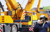 Engineer with large mobile construction cranes — Stock Photo