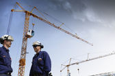 Building workers and giant mobile cranes — Stock Photo