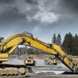Royalty-Free Stock Photo: Bulldozers in action, dark clouds moving in