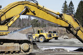 Bulldozers in action, dark clouds moving in — Stock Photo