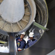 Stock Photo: Airplane mechanics servicing a jet engine