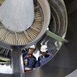 Airplane mechanics servicing a jet engine — Stock Photo