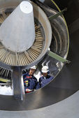 Airplane mechanics servicing a jet engine — Stockfoto