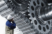 Gears and cogwheels operated by industry worker — Stock Photo