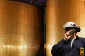 Oil and gas engineer with fuel tanks — Stock Photo
