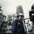Stock Photo: Oil and gas workers in front of oil refinery