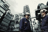 Oil and gas workers in front of oil refinery — Stock Photo