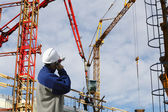Site-worker directing cranes — Stock Photo