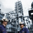Oil and gas workers and large refinery industry — Stock Photo