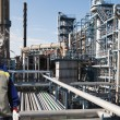 Stock Photo: Oil and gas engineer with giant refinery industry in background