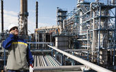 Oil and gas engineer with giant refinery industry in background — Stock Photo