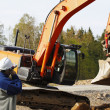 Industry worker directing large bulldozer and driver — Stock Photo
