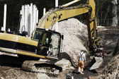 Digger and site worker in action — Stock Photo