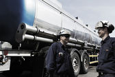 Oil workers re-fueling large truck — Stock Photo