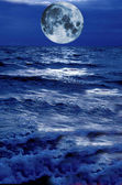 Moon rise over stormy blue waters — Stock Photo