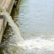 Flow out water from the conduit to the river — Stock Photo