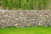 Fence real stone wall surface with cement on green grass field — Stockfoto