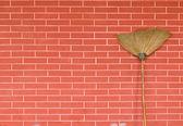 Broom on brick wall — Stock Photo