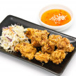 Fried chicken in black plate with sauce — Stock Photo
