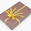 Black gift box with white bar attached gold ribbon — Stock Photo #35197059