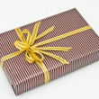 Black gift box with white bar attached gold ribbon — Stock Photo #35197101