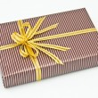 Black gift box with white bar attached gold ribbon — Stock Photo #35197111