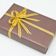 Black gift box with white bar attached gold ribbon — Stock Photo #35197223