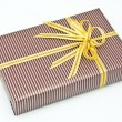 Black gift box with white bar attached gold ribbon — Stock Photo #35197491