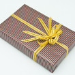 Black gift box with white bar attached gold ribbon — Stock Photo #35197497