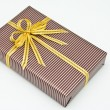 Black gift box with white bar attached gold ribbon — Stock Photo #35197511