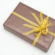 Black gift box with white bar attached gold ribbon — Stock Photo #35198699