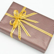 Black gift box with white bar attached gold ribbon — Stock Photo #35199349