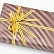 Black gift box with white bar attached gold ribbon — Stock Photo #35199501