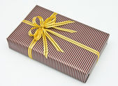 Black gift box with white bar attached gold ribbon — ストック写真