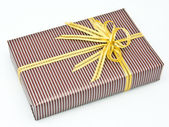 Black gift box with white bar attached gold ribbon — Стоковое фото