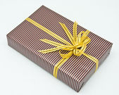 Black gift box with white bar attached gold ribbon — Stok fotoğraf
