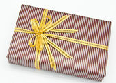 Black gift box with white bar attached gold ribbon — Zdjęcie stockowe
