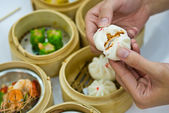 Steamed dumpling with hand — Stock Photo