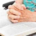 Praying Senior Hands on Bible — Stock Photo