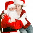 Girl Sitting on Santas Lap Getting a Hug - Stock Photo