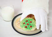 Santas Hand Reaching for Christmas Cookie — Stock Photo