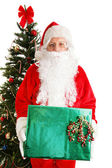 Santa by Christmas Tree with Gift — Stock Photo
