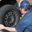 Auto Mechanic Removing Tire - Stock Photo