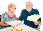 Senior koppel bedroefd door medische rekeningen — Stockfoto