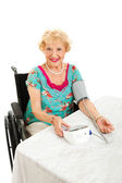 Beautiful Senior Takes Own Blood Pressure — Stock Photo